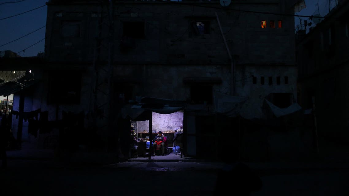 A Palestinian man sits as he sells vegetables in a makeshift shop lit with a lamp powered by a battery during a power cut in Beit Lahiya in the northern Gaza Strip January 11, 2017. Picture taken January 11, 2017. REUTERS/