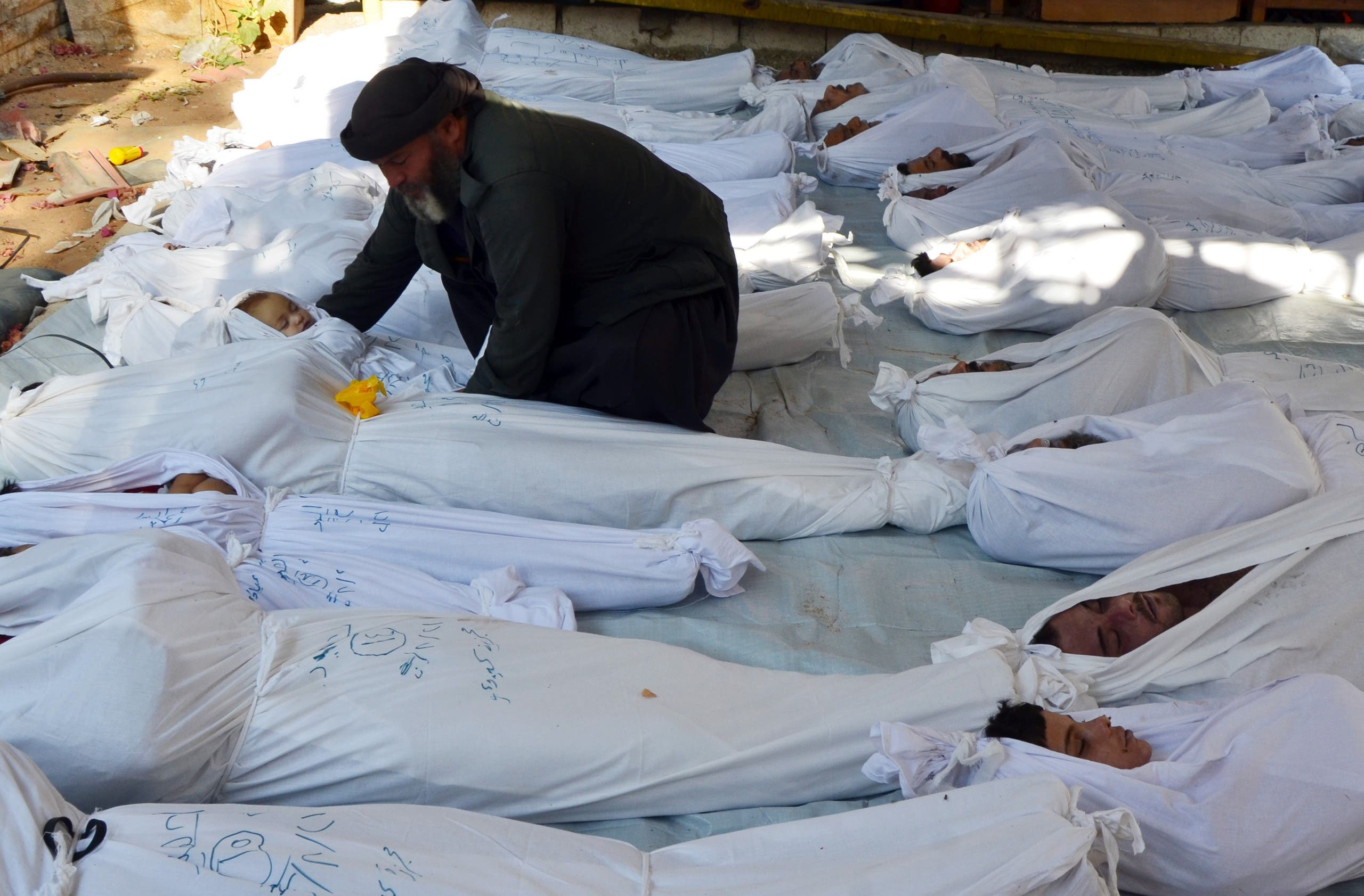 A man holds the body of a dead child among bodies of people activists say were killed by nerve gas in Ghouta, a rebel-controlled suburb of the Syrian capital Damascus, Syria August 21, 2013. REUTERS