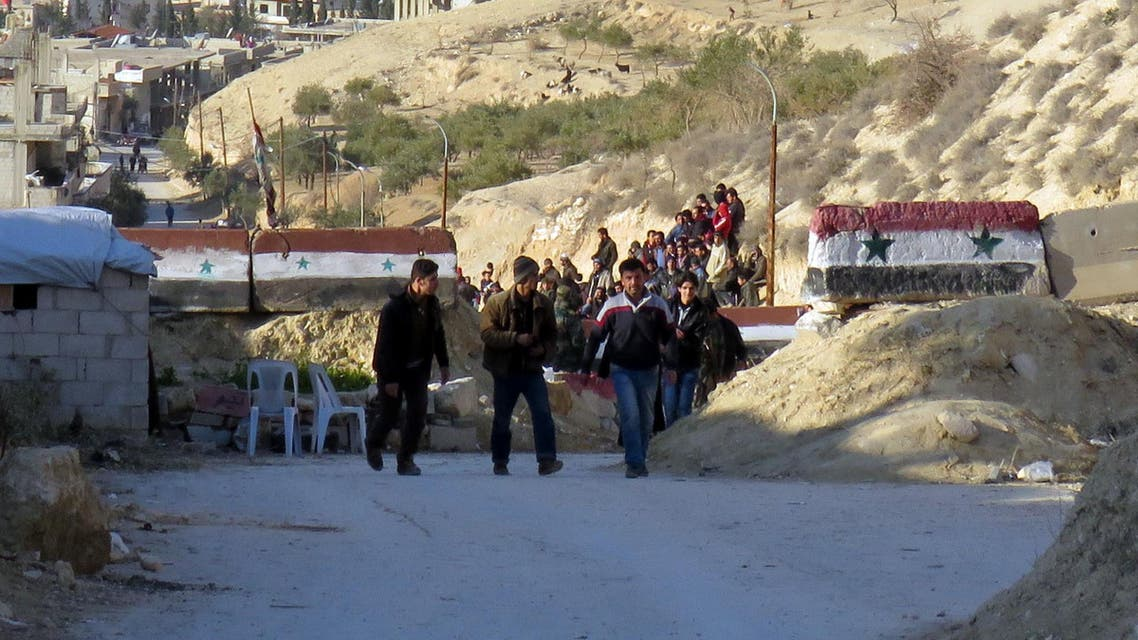 People are seen crossing at an army checkpoint, as rebel fighters and their families prepare to leave the town of Deir Kanun in the Wadi Barada region, on January 11, 2017,