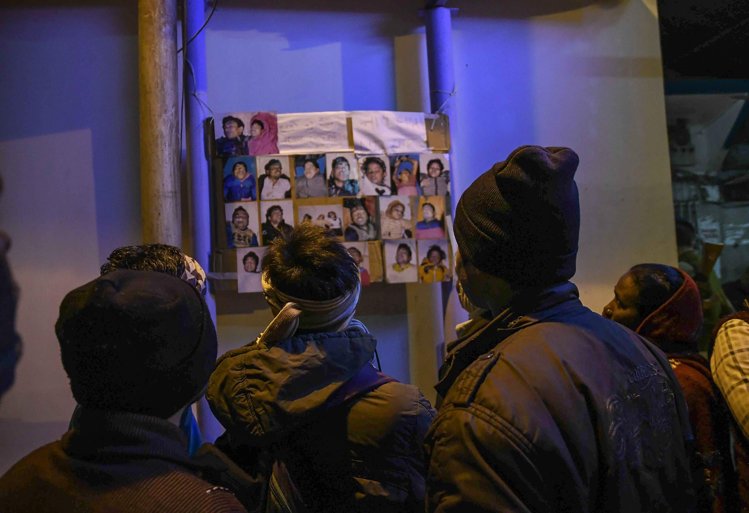 ذوو الضحايا ينظرون إلى صور الجثث التي تم انتشالها