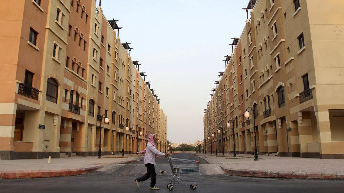 A man pushes a cart as he walks past residential buildings in Riyadh, Saudi Arabia. (Reuters)