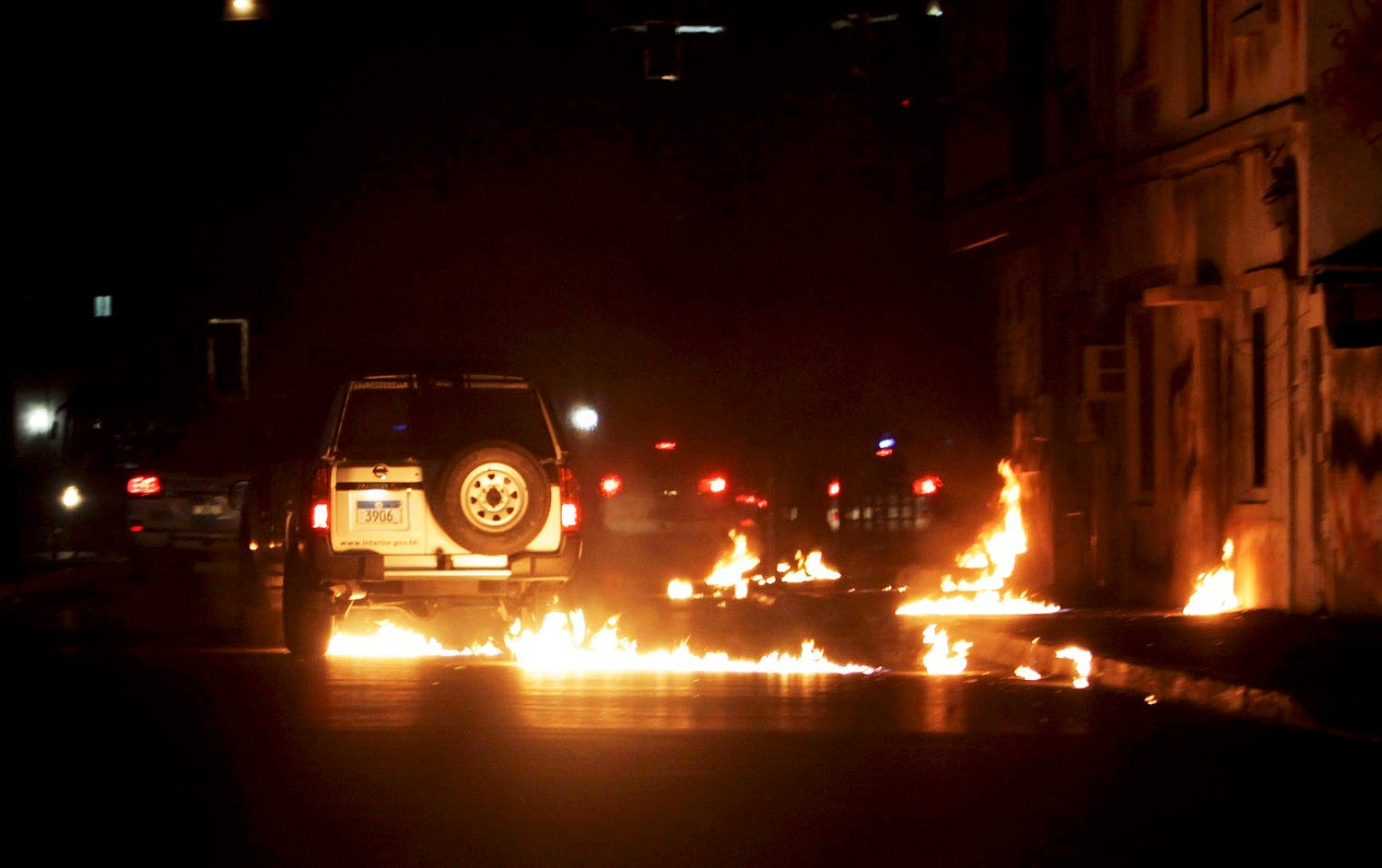 Molotov cocktails thrown by anti-government protesters, unseen, who ran out from narrow side streets to strike a passing police convoy, burn on the road in this image taken through a car windshield in Daih village. (File photo: AP)