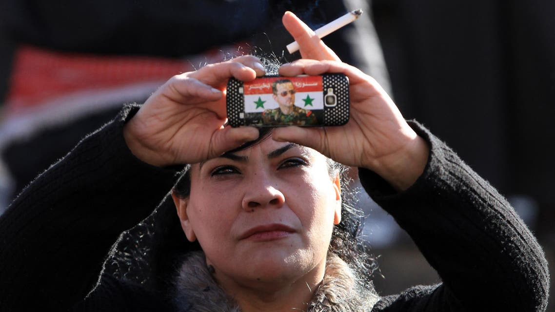 Syrian government supporter takes pictures with her mobile phone bearing a sticker of Syrian President Bashar al-Assad during a pro-regime rally in Damascus on January 27, 2012. AFP