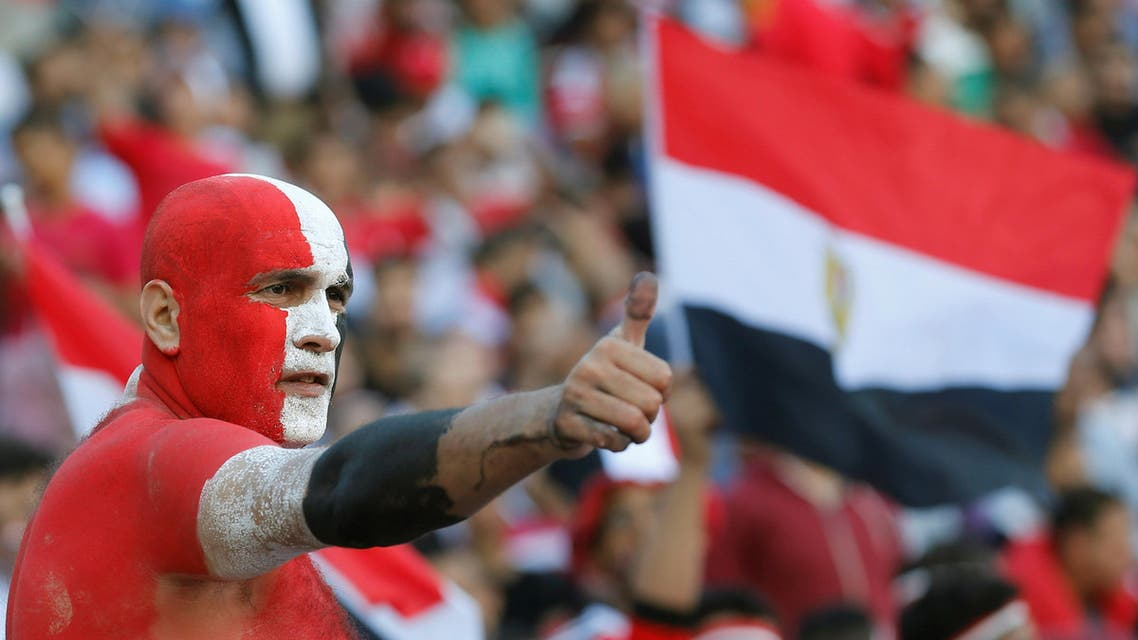 An Egyptian fan painted in the colours of the national flag cheers with others during the game against Ghana. REUTERS