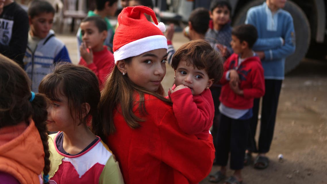 """Chloe, a Lebanese Christian teenager dressed as Santa Claus, holds a Syrian refugee on December 24, 2016 during a gift distribution organised by the maronite congregation """"Mission de Vie"""" in a slum in the town of Dbayeh, north of Beirut. (AFP)"""