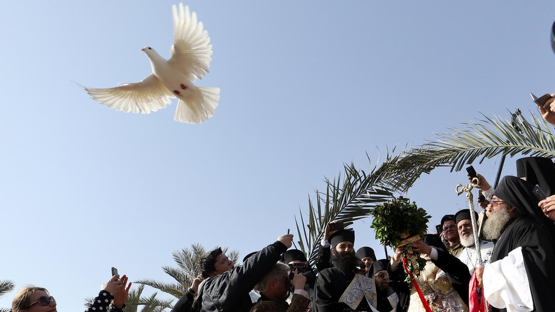 Greek Orthodox Patriarch of Jerusalem Theophilos III (C) releases a dove as he blesses the water of the Jordan River during the Epiphany celebrations at the Qasr al-Yahud baptismal site near the West Bank city of Jericho on January 18, 2017. (AFP)