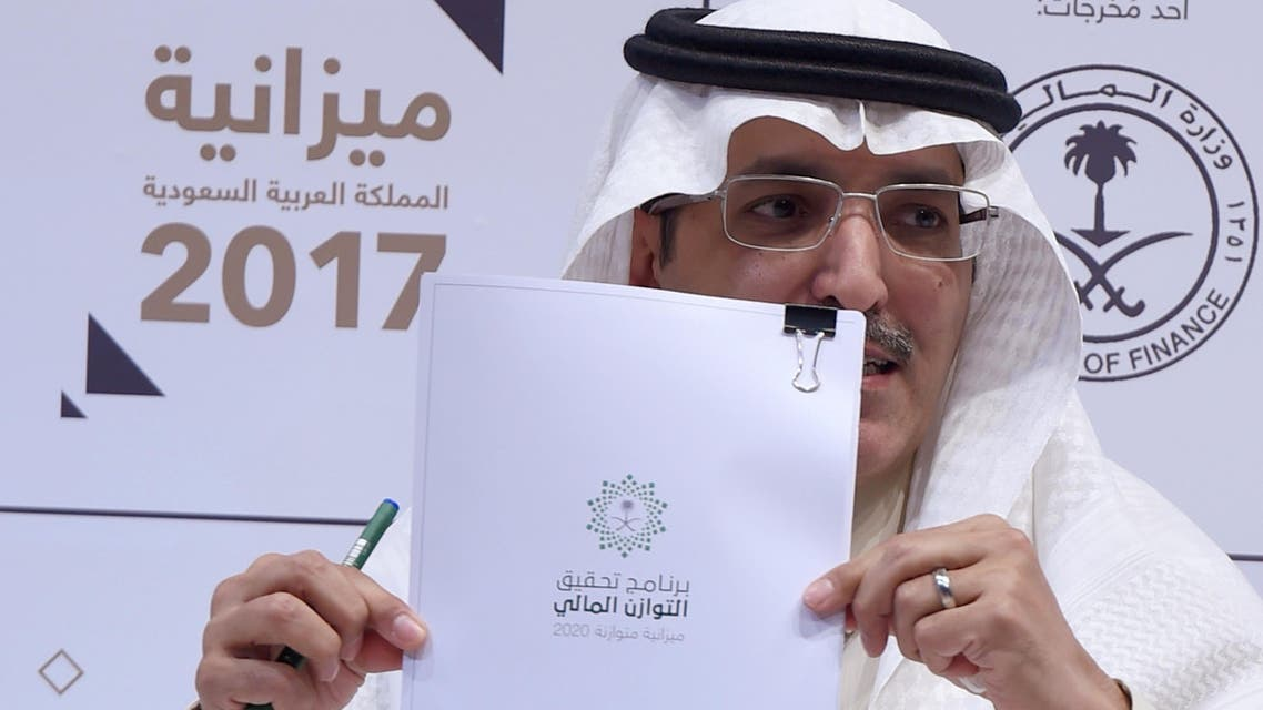 Saudi Finance Minister Mohammed Al-Jadaan shows documents during a press conference to unveil the country's national budget for 2017 on December 22, 2016 in Riyadh. (AFP)
