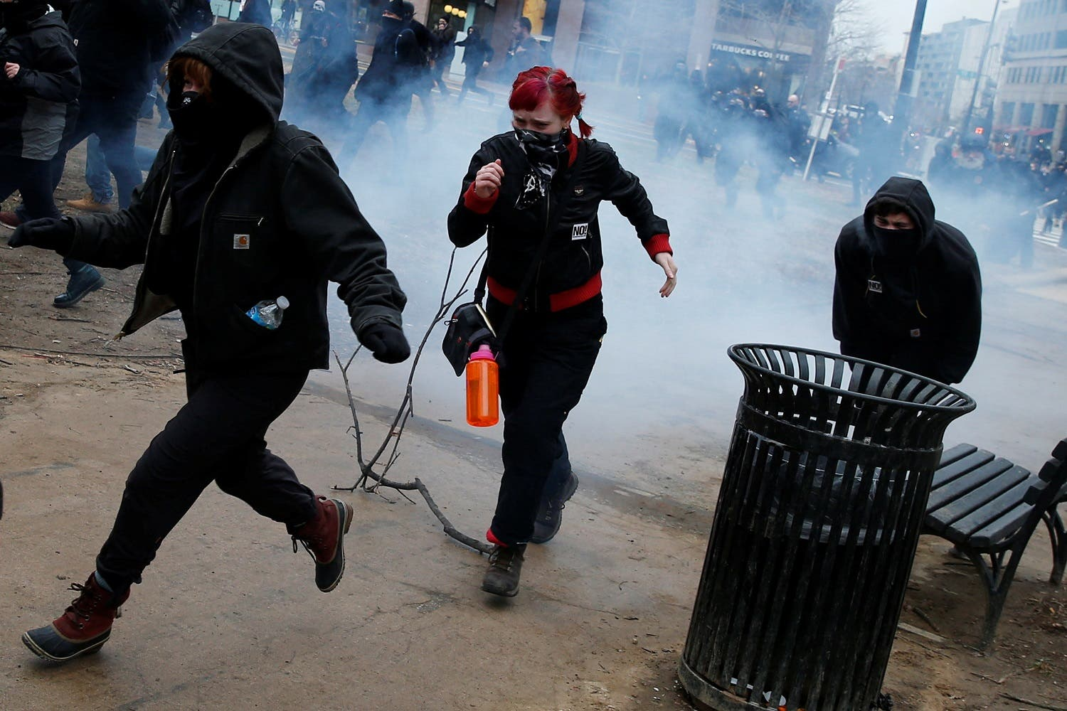 Activists run after being hit by a stun grenade while protesting against Trump on the sidelines of the inauguration in Washington. (Reuters)