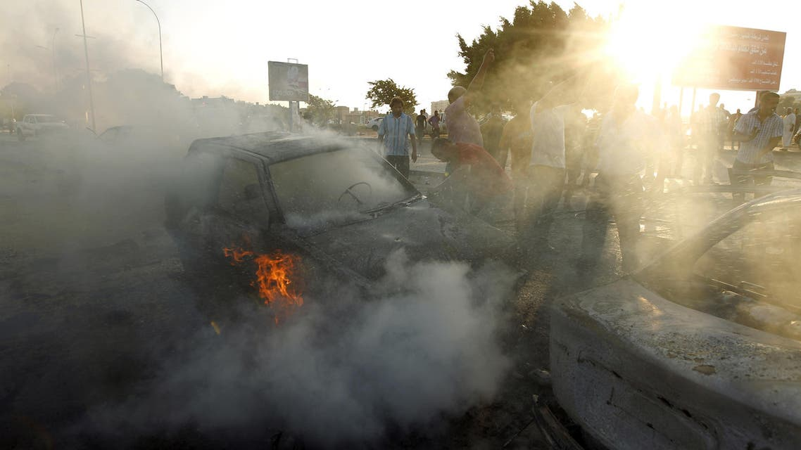 People gather around a burning car at the site of a car bomb during a demonstration in support of General Khalifa Haftar, in the coastal city of Benghazi on September 16, 2016. AFP