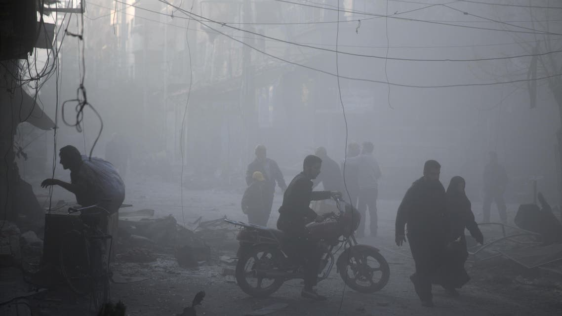 Syrians walk in a dusty street following air strikes by suspected Russian planes on the central rebel-held town of Douma, on the outskirts of the capital Damascus, on November 7, 2015. AFP