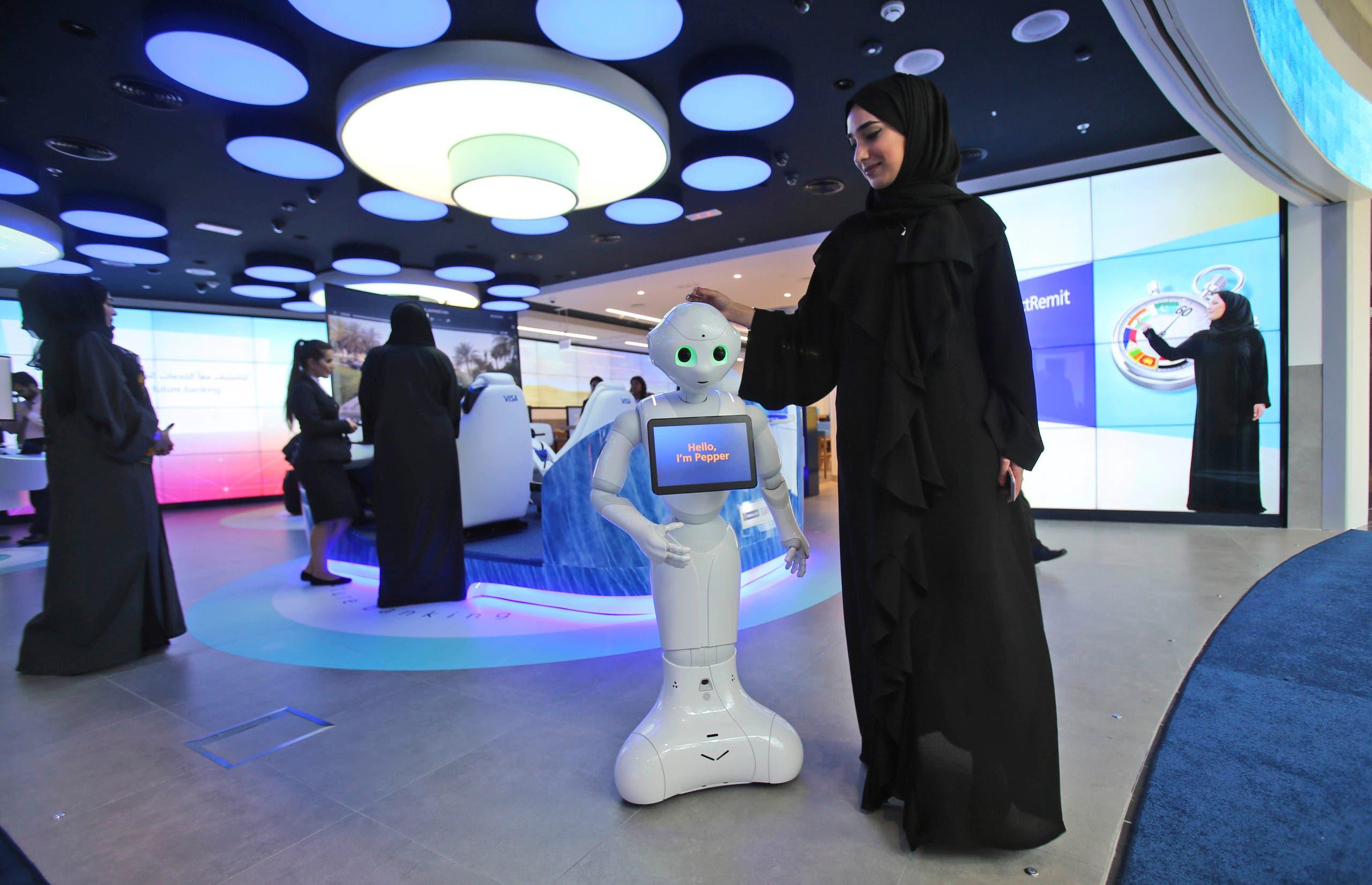 An Emirati woman presents Pepper, a robot, at a bank, as a part of the Dubai Future Accelerators in Dubai, UAE, on Oct. 4, 2016. (AP)
