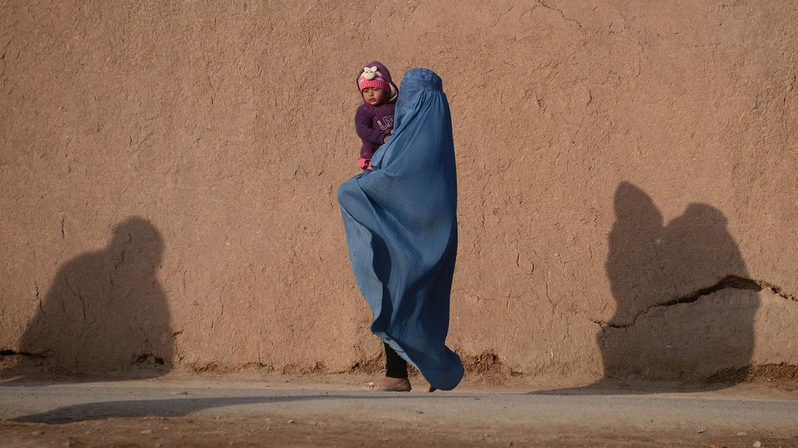 In this photograph taken on January 19, 2017, an Afghan burqa-clad woman carries a child as she walks along a road (File Photo: Aref Karimi/AFP)