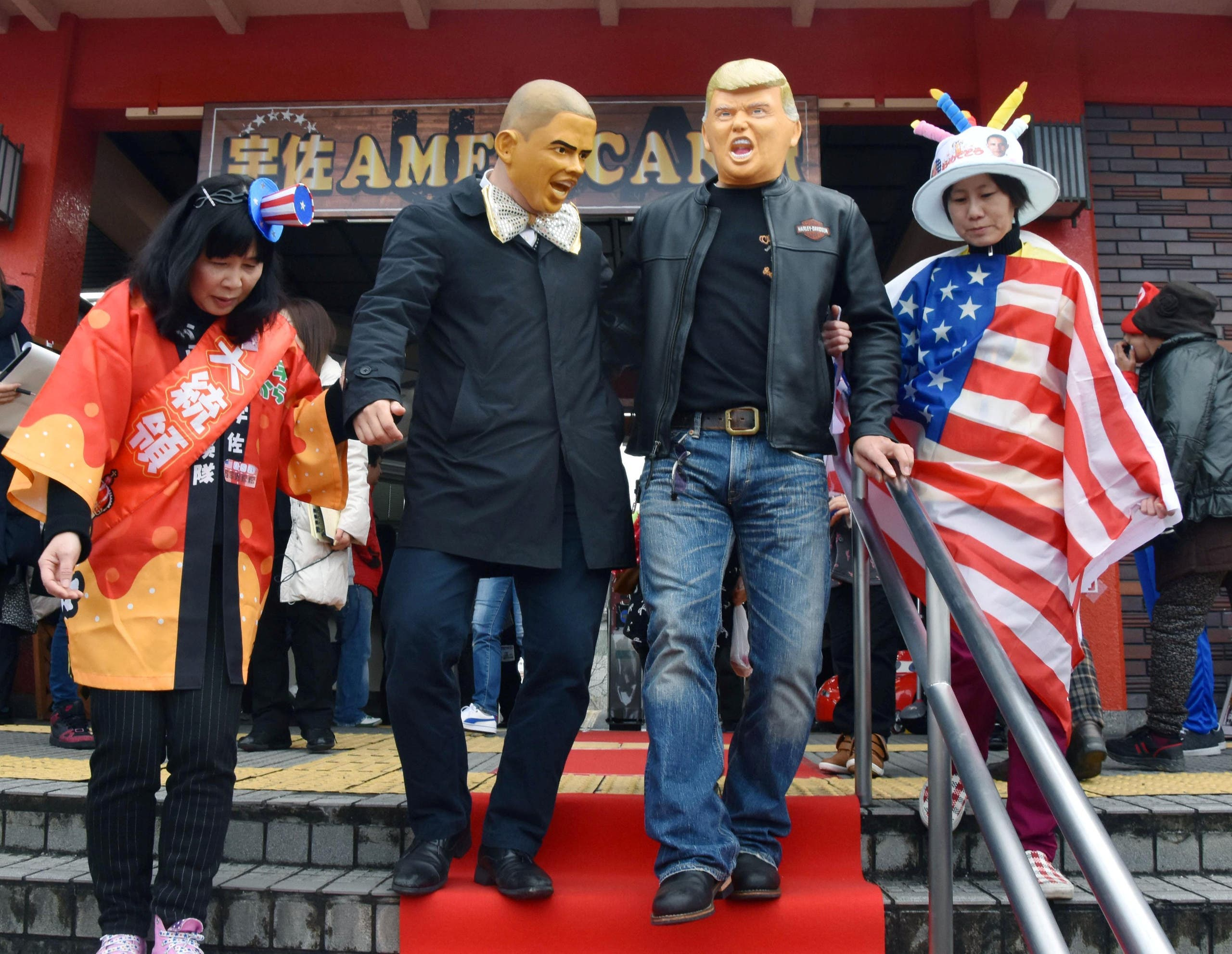 People wearing Barack Obama and Donald Trump masks walk down the stairs at JR Usa Station in the city of Usa in Oita Prefecture, southwestern Japan, in this photo taken by Kyodo on January 21, 2017. (Reuters)