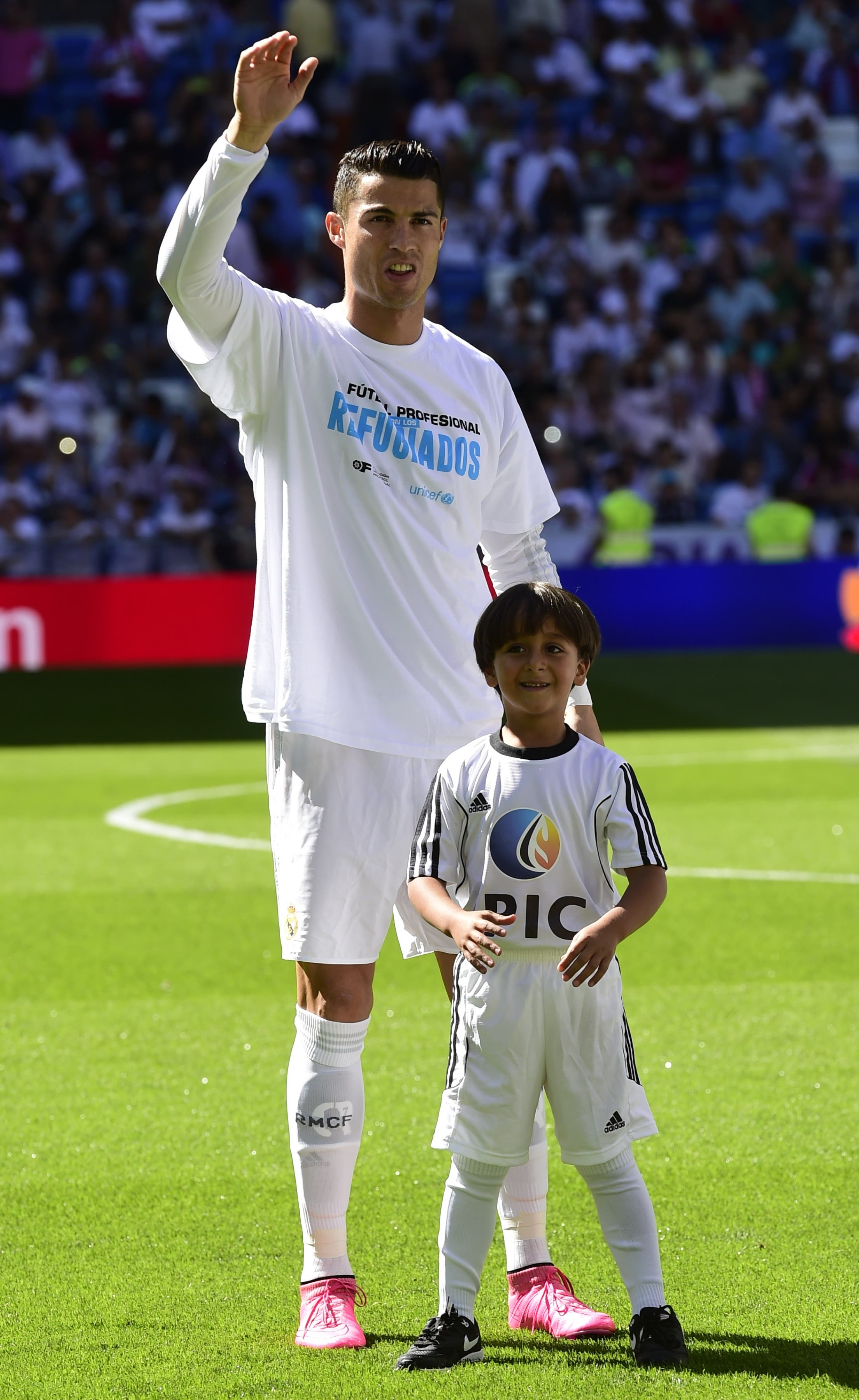 Real Madrid's Portuguese forward Cristiano Ronaldo (L) poses with Zaid, son of Osama Abdul Mohsen (C), the Syrian refugee who made world headlines when a Hungarian journalist tripped him over as he fled, before the Spanish league football match Real Madrid CF vs Granada FC at the Santiago Bernabeu stadium in Madrid on Spetember 19, 2015. AFP PHOTO/ JAVIER SORIANO
