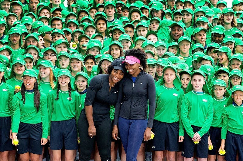 Serena and Venus Williams stand together with Australian Open tennis tournament ballboys and girls during a promotional event at Melbourne Park. (Reuters)