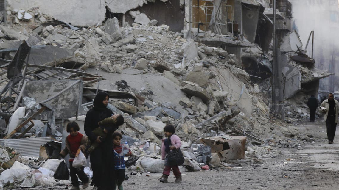 Syrians walk amid destroyed buildings as residents return to Aleppo's formerly rebel-held al-Shaar neighbourhood on January 21, 2017, a month after government forces retook the northern Syrian city from rebel fighters. AFP