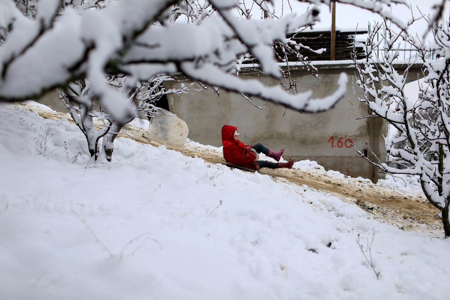 A girl uses a plastic sack to slide down a snow-covered slope after a snowfall on the outskirts of Medea. (Reuters)