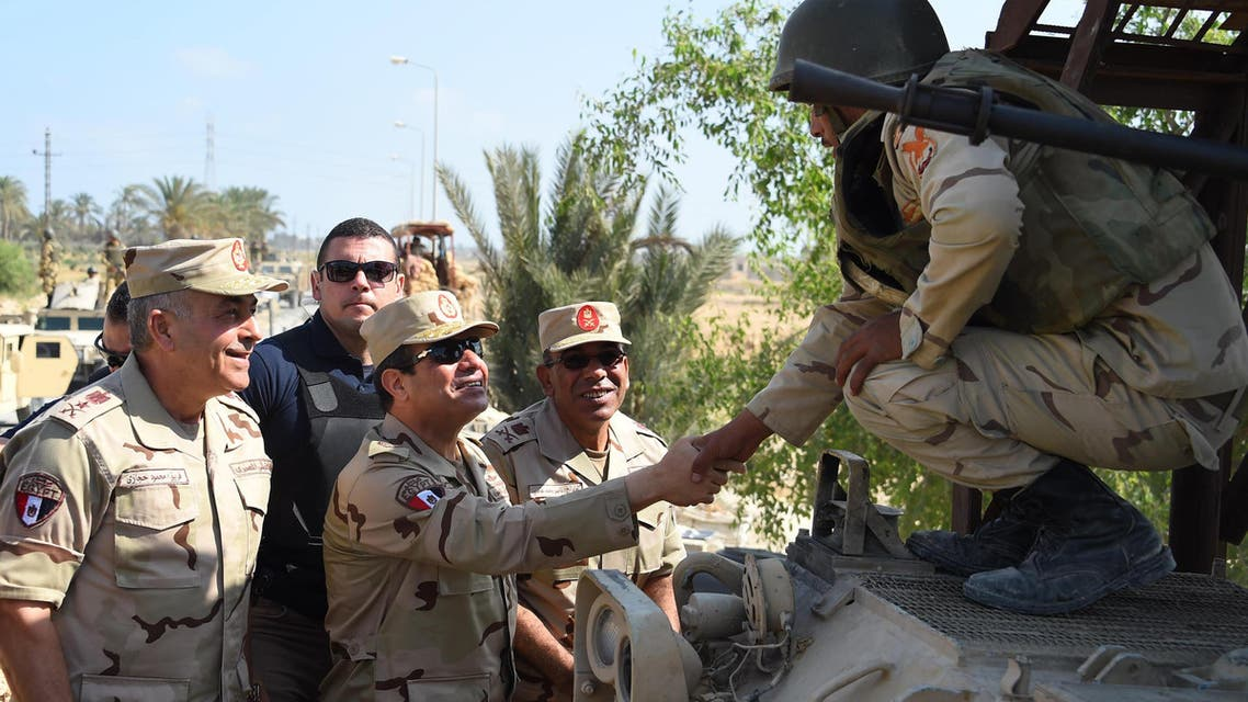A handout picture released by the Egyptian Presidency on July 4, 2015, shows Egyptian President Abdel Fattah el-Sisi (C) shaking hands with a member of the security forces during a visit to the Sinai Peninsula following a wave of deadly attacks on armed forces by ISIS militants. (AFP)