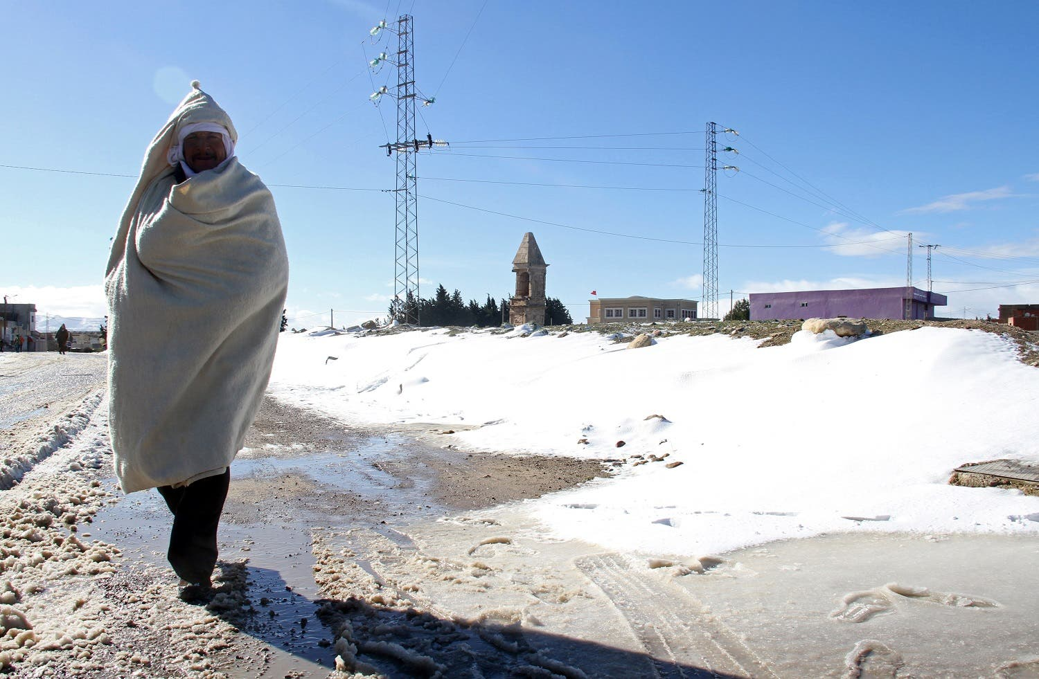A Tunisian man walks in the snow in the town of Maktar in Tunisia's central Siliana region on January 16, 2017. (AFP)