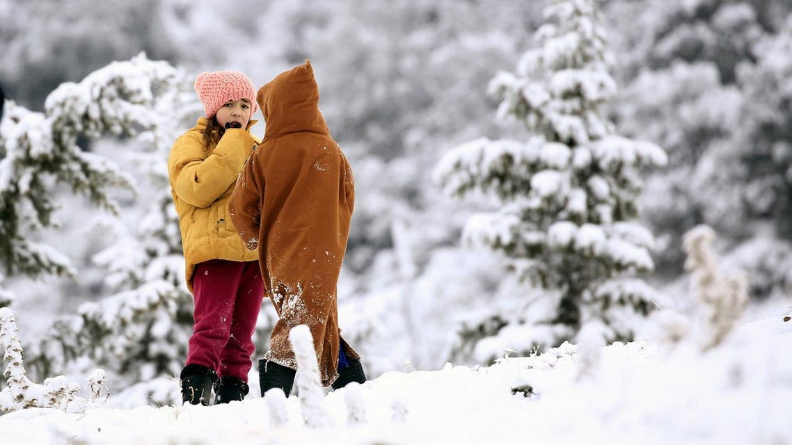 Children talk to each other as they stand outside their house after a snowfall near Medea, Algeria. (Reuters)