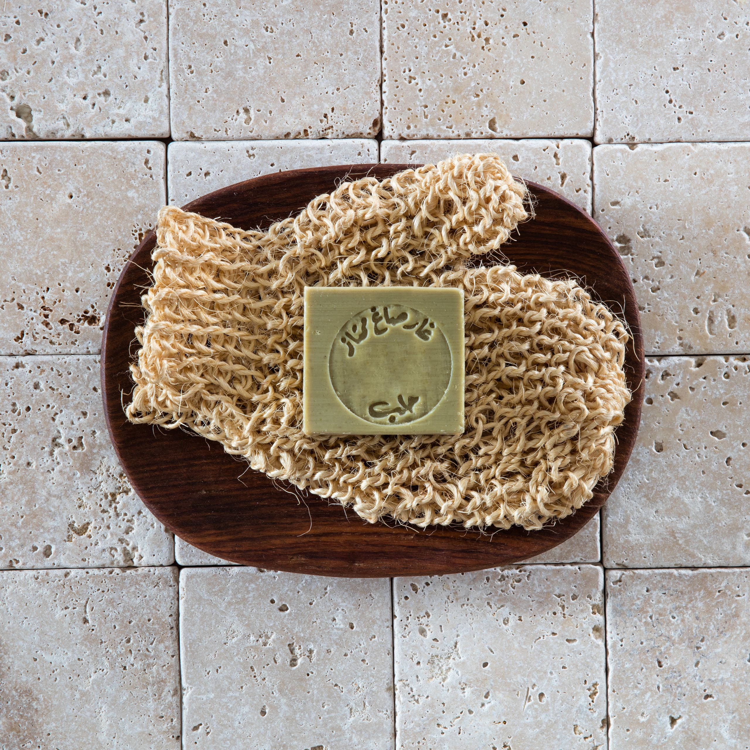 flat lay of green Aleppo soap on loofah mitt in beautiful dark wooden bowl. shutterstock