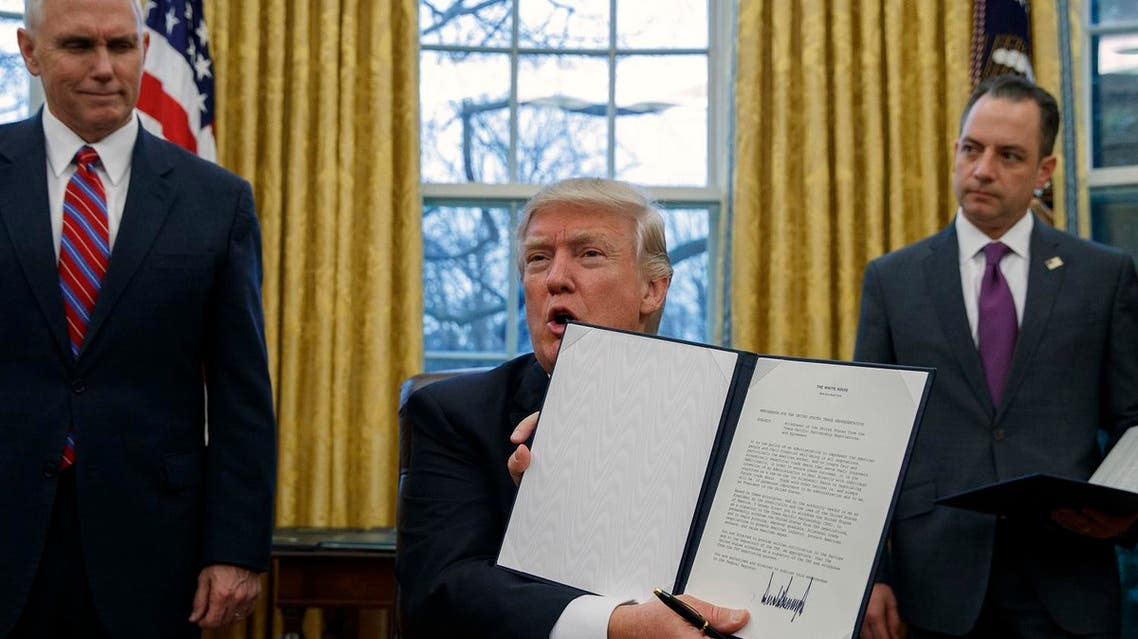 Vice President Mike Pence, left, and White House Chief of Staff Reince Priebus, right, watch as President Donald Trump shows off an executive order to withdraw the US from the 12-nation Trans-Pacific Partnership trade pact agreed to under the Obama administration (Photo: AP/Evan Vucci)