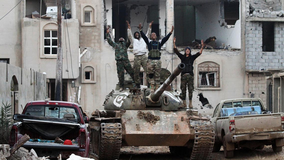 Members of the Libyan National Army (LNA) wave from a tank as they hold a position during fighting against jihadists in Qanfudah, on the southern outskirts of Benghazi, on January 14, 2017