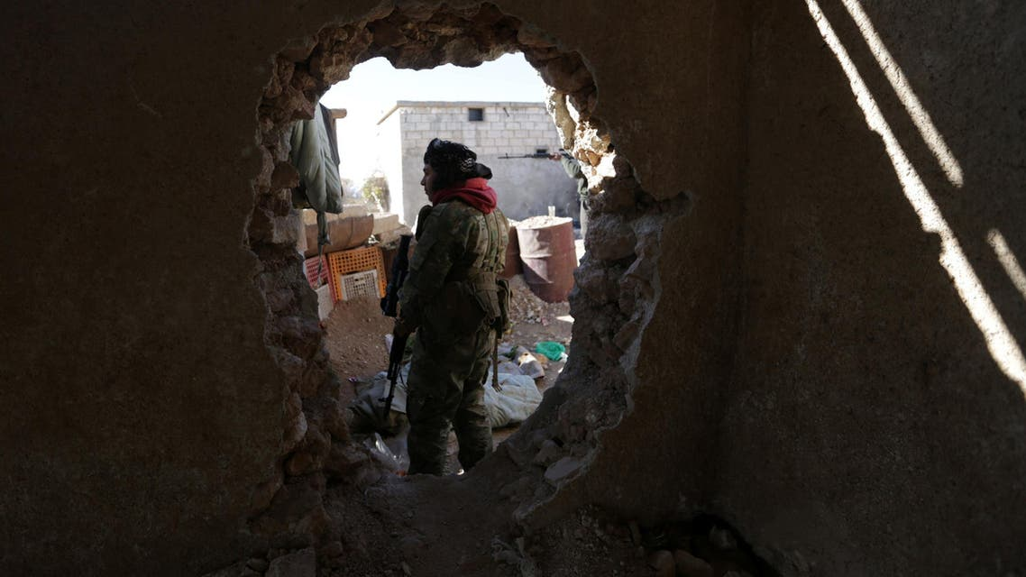 A rebel fighter stands near a hole in the wall as he carries his weapon on the outskirts of Al-Bab town in Syria January 22, 2017. REUTERS