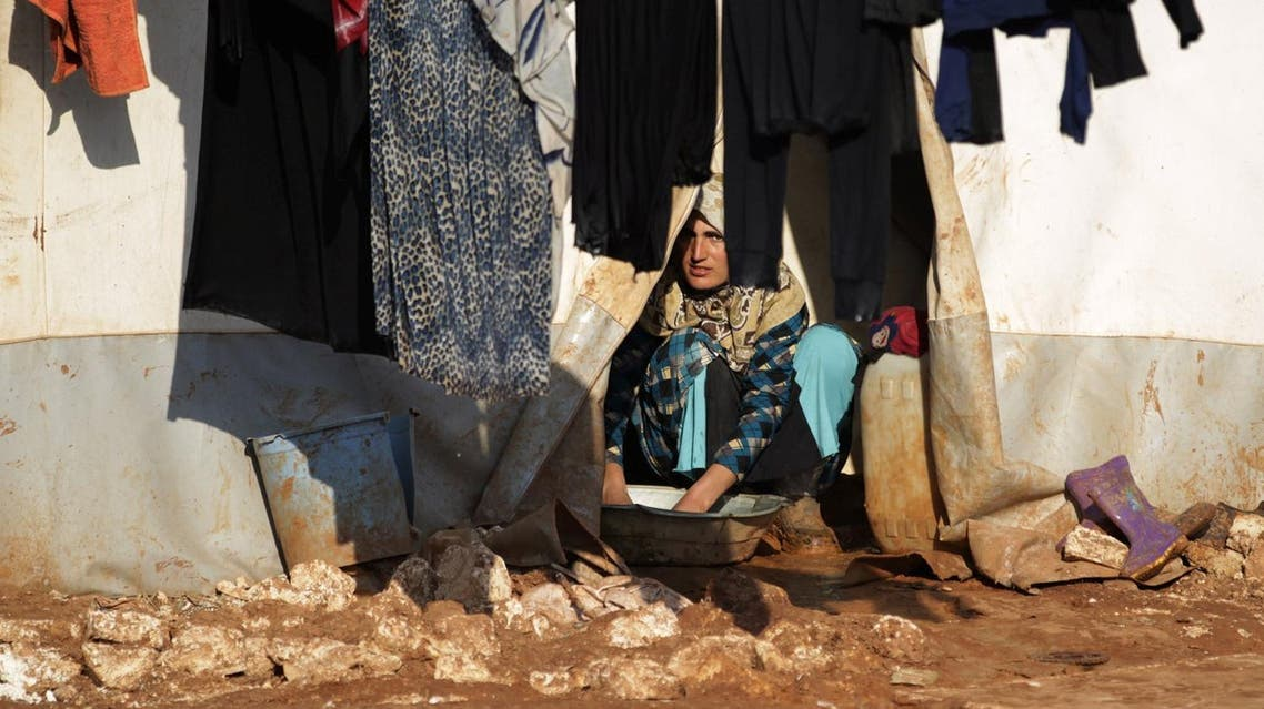 An internally displaced Syrian woman washes clothes inside her tent at the Bab Al-Salam refugee camp, near the Syrian-Turkish border. (Reuters)