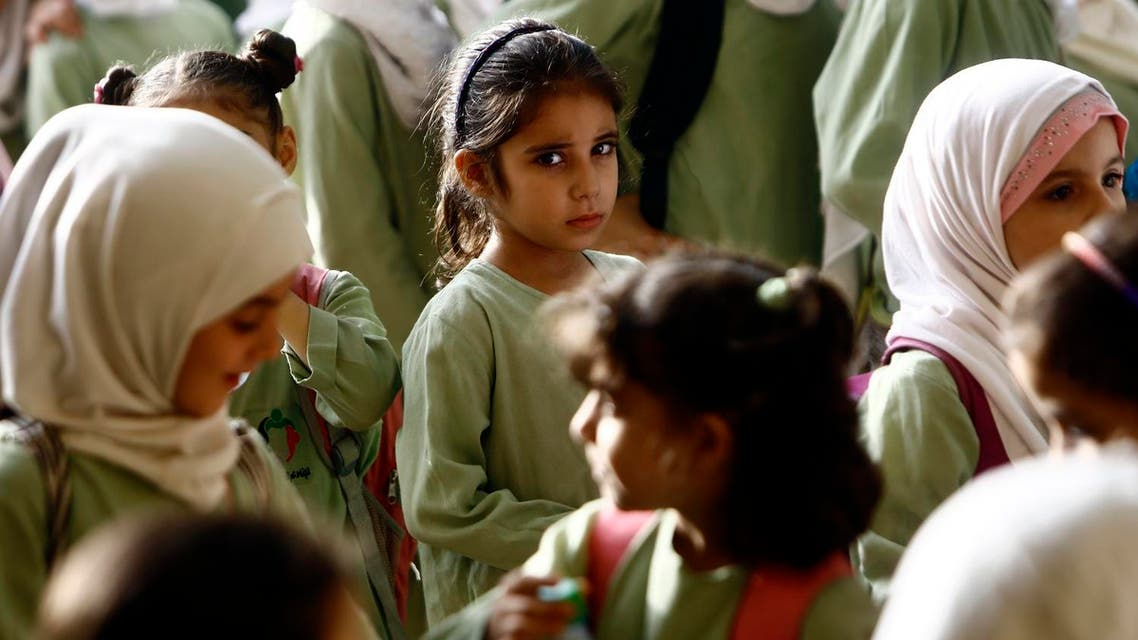 Syrian girls, who fled the ongoing conflict in Syria, stand in line at an all girls school in the south of Khartoum. (AFP)