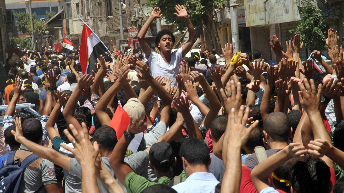 Egyptian supporters of the Muslim Brotherhood movement shout slogans during a rally to mark the first anniversary of the military ouster of president Mohamed Morsi on July 3, 2014 in Cairo's Mattarya district. (AFP)