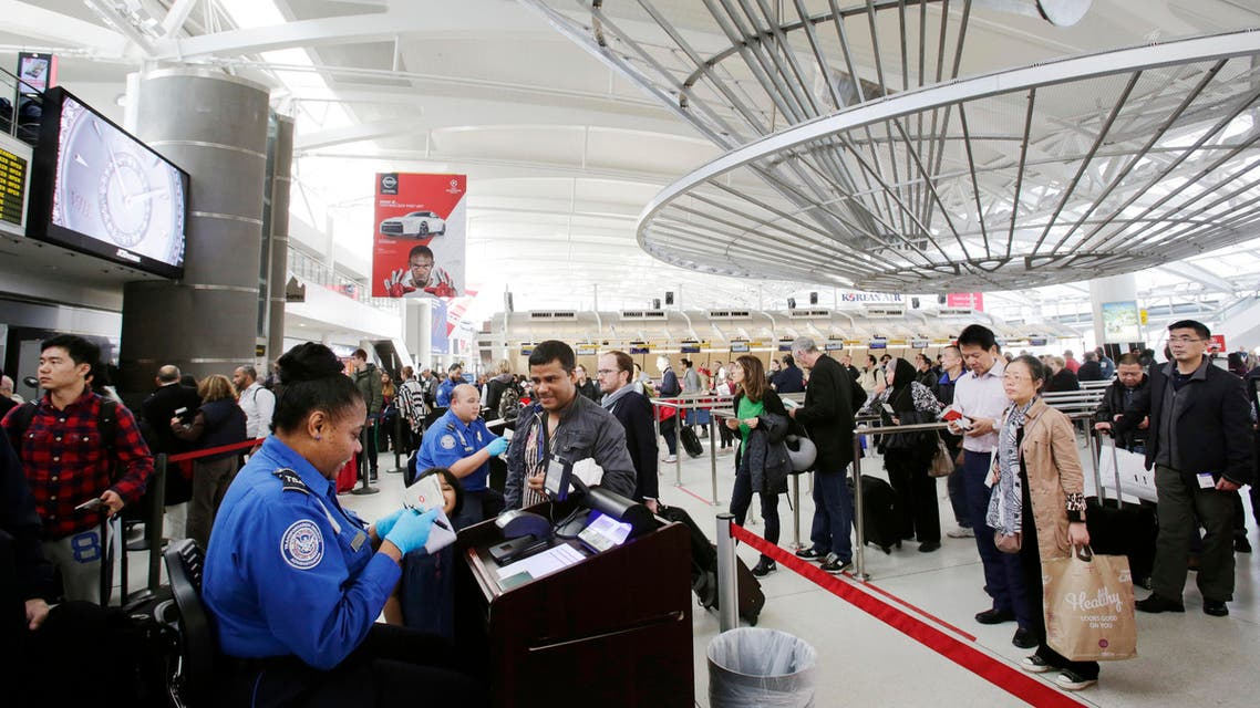 In this Oct. 30, 2014, file photo, a TSA officer, left, checks a passenger's ticket, boarding pass and passport as part of security screening at John F. Kennedy International Airport in New York. (AP)