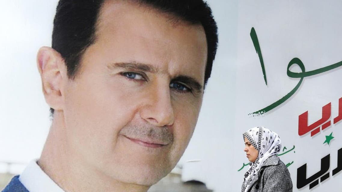 A Syrian woman walks past a placard bearing a portrait of President Bashar al-Assad in the city of Damascus. (AFP)