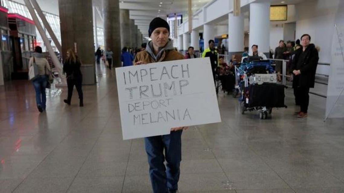 محتج يرفع لافتة تندد بقرار ترامب بشأن حظر السفر ضد مواطني سبع دول في صالة السفر رقم 4 في مطار جون كنيدي في كوينز بنيويورك يوم السبت