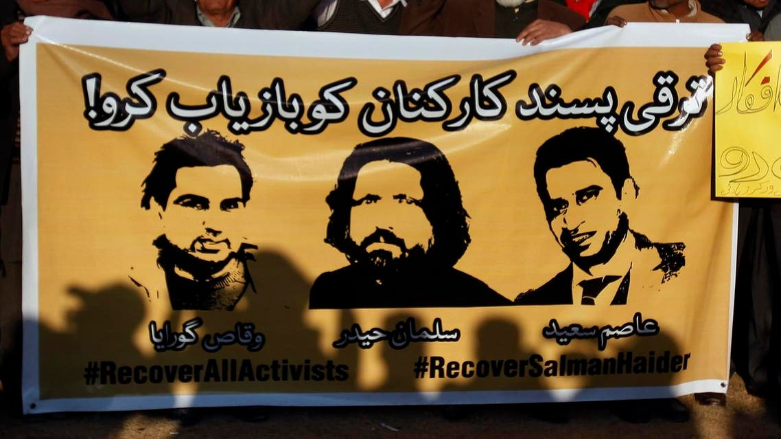 members of civil society hold a banner with pictures of missing rights activists, Waqas Goraya, Salman Haider, and Asim Saeed, during a demonstration. (AP)