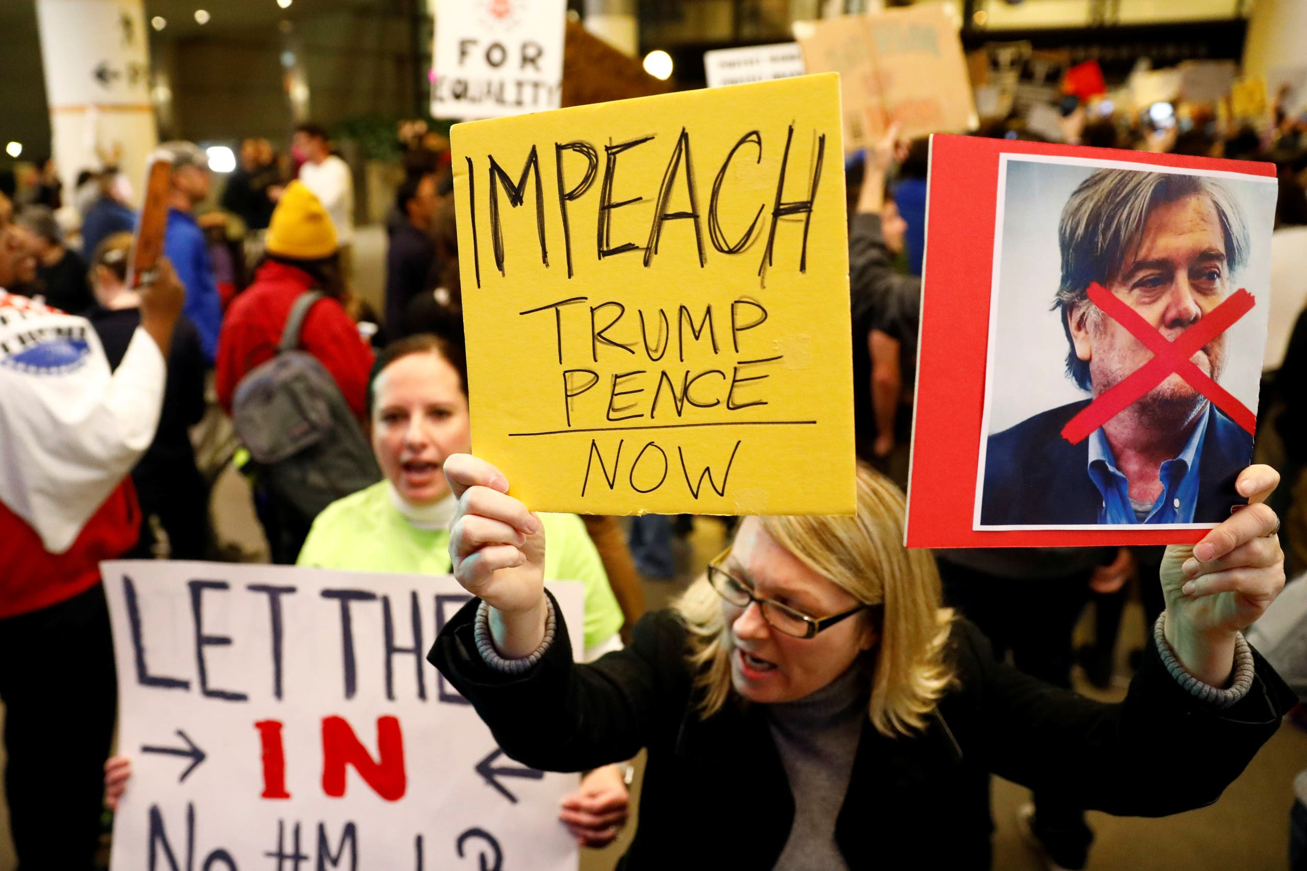 A woman holds signs against Steve Bannon and encouraging the impeachment of Trump and Pence during a protest of Donald Trump's travel ban from Muslim majority countries at the International terminal at Los Angeles International Airport (LAX) in Los Angeles, California, U.S., January 28, 2017. REUTERS/Patrick T. Fallon