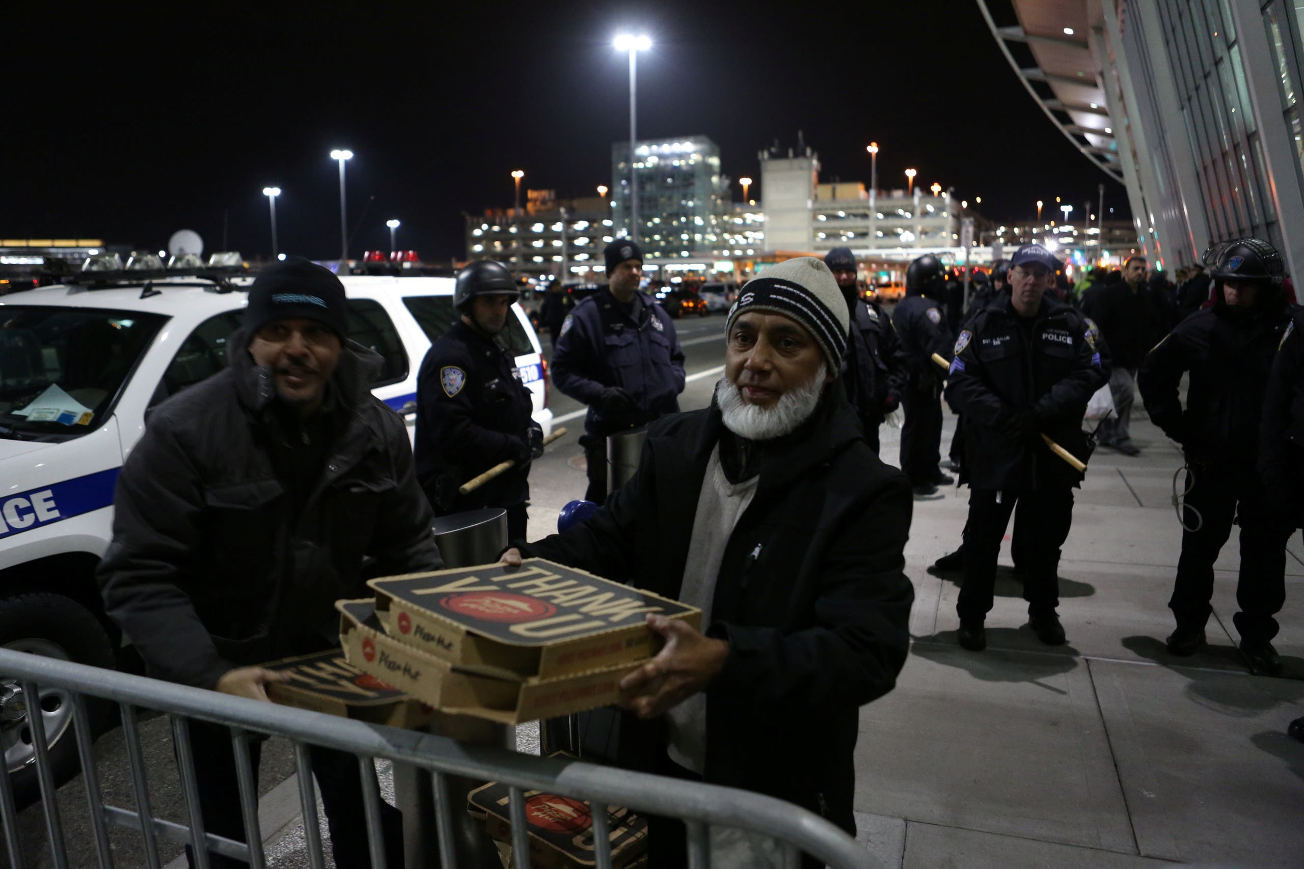 A man gives pizza to protesters chanting slogans in opposition to U.S. President Donald Trump's ban on immigration and travel outside Terminal 4 at JFK airport in Queens, New York City, New York, U.S. January 28, 2017. REUTERS/Joe Penney