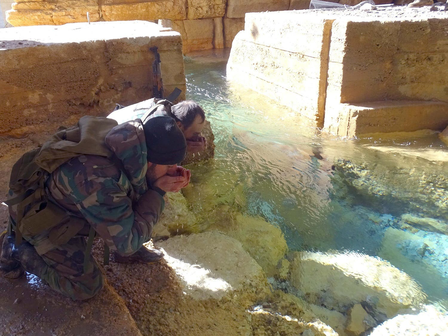 Syrian government soldiers drink from a water pumping station in the village of Ain al-Fija in the Wadi Barada valley near Damascus. (Reuters)