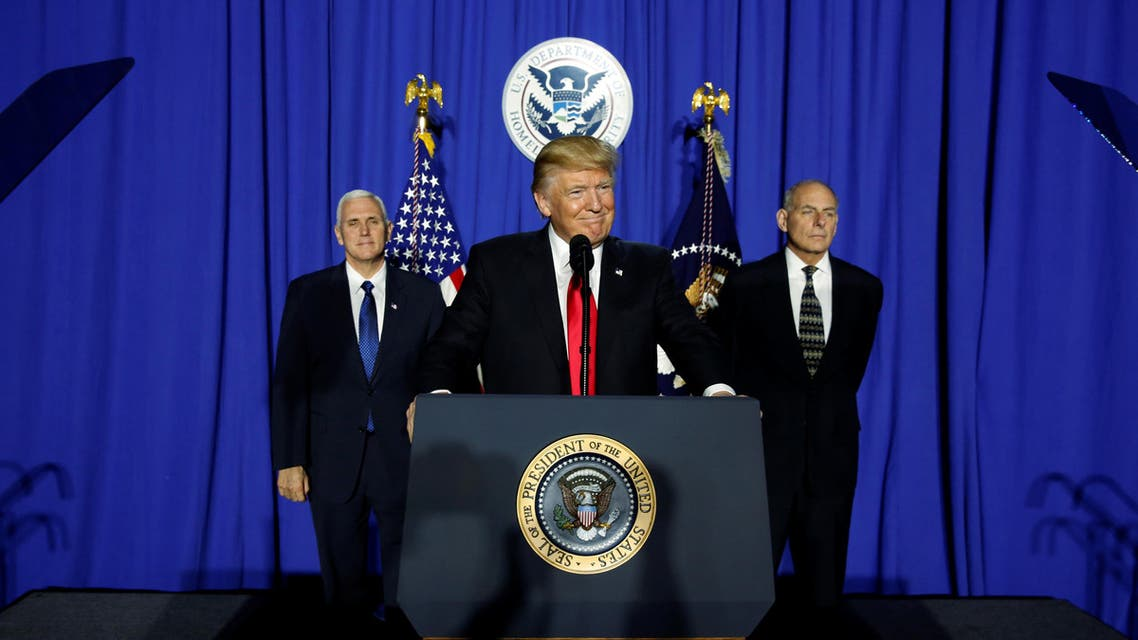 President Donald Trump (C), flanked by Vice President Mike Pence (L) and Homeland Security Secretary John Kelly (R), takes the stage to deliver remarks at Homeland Security headquarters in Washington, U.S. January 25, 2017.