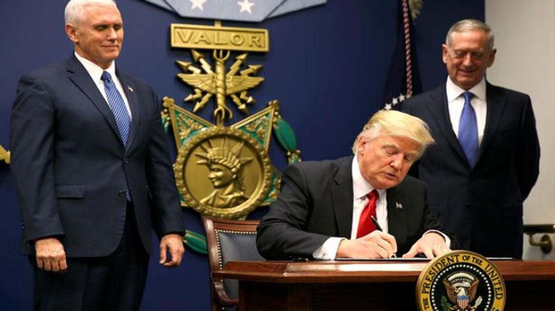بانس (الى اليسار) ومعه ماتّيس، يبتسمان خلف ترمب وهو يوقع المرسوم المانع مسلمي 7 دول من دخول أميركا