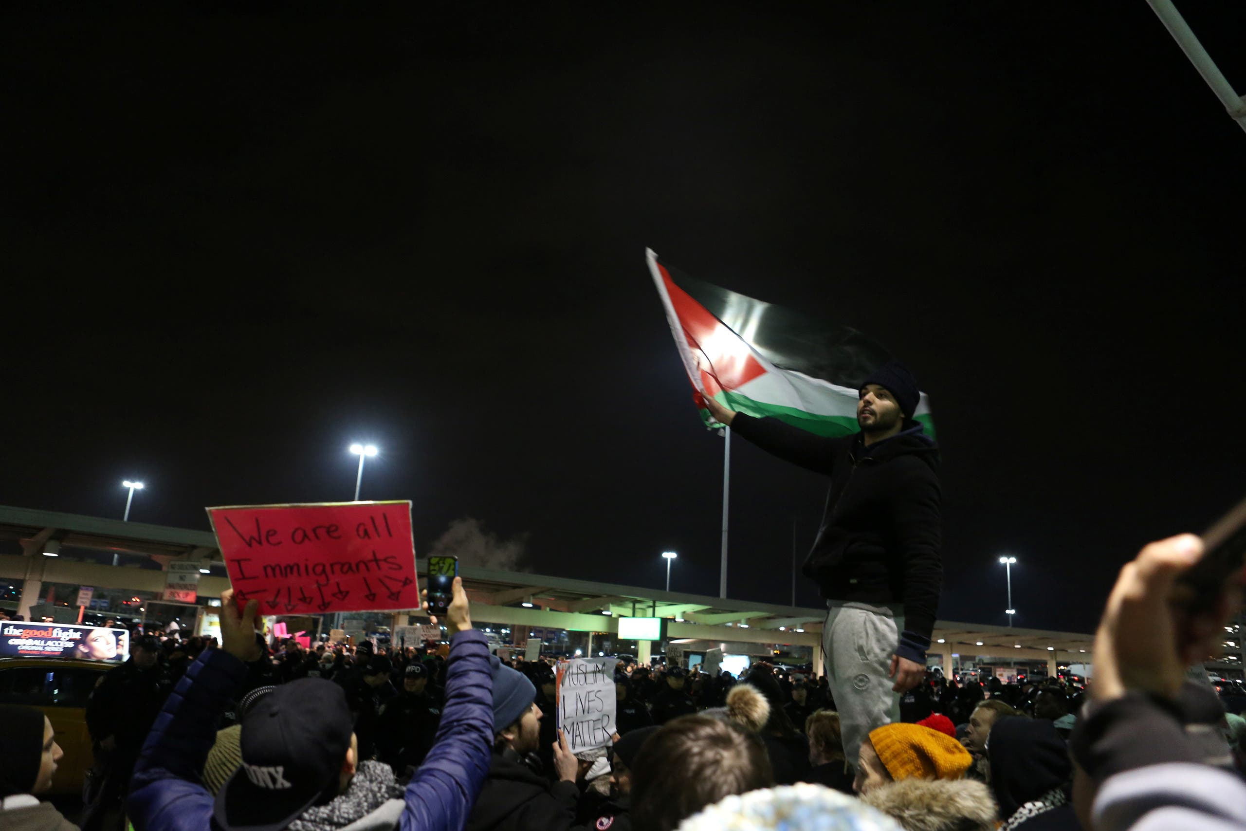 A protester waves a Palestinian flag in opposition to U.S. President Donald Trump's ban on immigration and travel outside Terminal 4 at JFK airport in Queens, New York City, New York, U.S. January 28, 2017. REUTERS/Joe Penney