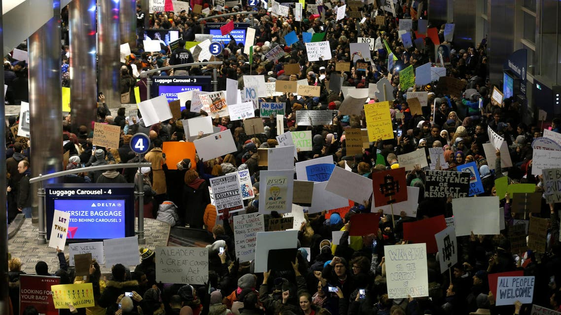 Hundreds of people rally against a temporary travel ban signed by U.S. President Donald Trump in an executive order, during a protest at the baggage claim area at Detroit Metropolitan airport in Romulus