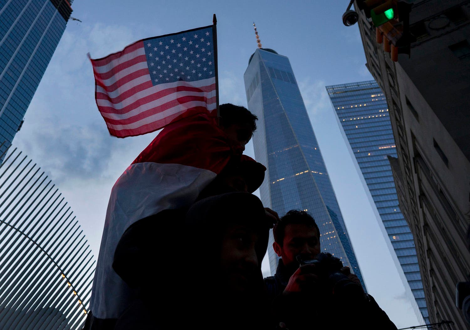 With One World Trade Center in the background, people march in New York, Sunday, Jan. 29, 2017, as they protest against President Donald Trump's executive order banning travel to the US by citizens of several countries. (AP Photo/Craig Ruttle)