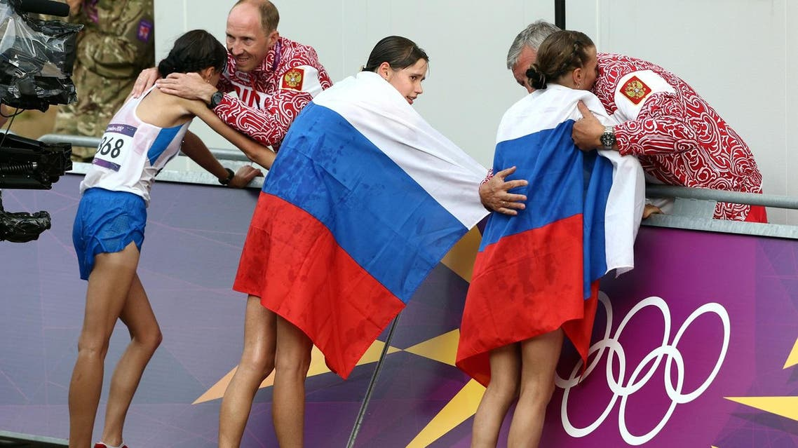 In this Aug. 11, 2012 file photo Russia coach Alexey Melnikov congratulates Olga Kaniskina, right, and Russia men's gold medalist Sergey Kirdyapkin congratulates Anisya Kirdyapkina, left, after the women's 20-kilometers race walk at the 2012 Summer Olympics in London. (AP)