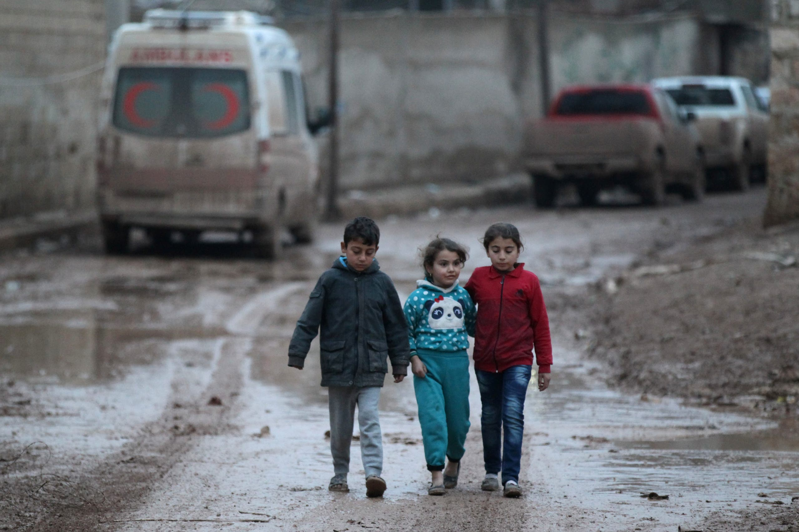 Children walk near a parked ambulance in al-Rai town, northern Aleppo province, Syria December 27, 2016. REUTERS/Khalil Ashawi