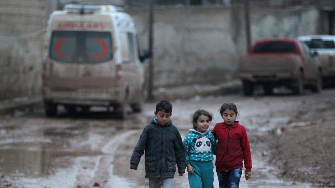 Children walk near a parked ambulance in al-Rai town, northern Aleppo province, Syria December 27, 2016. REUTERS/Khalil Ashawi