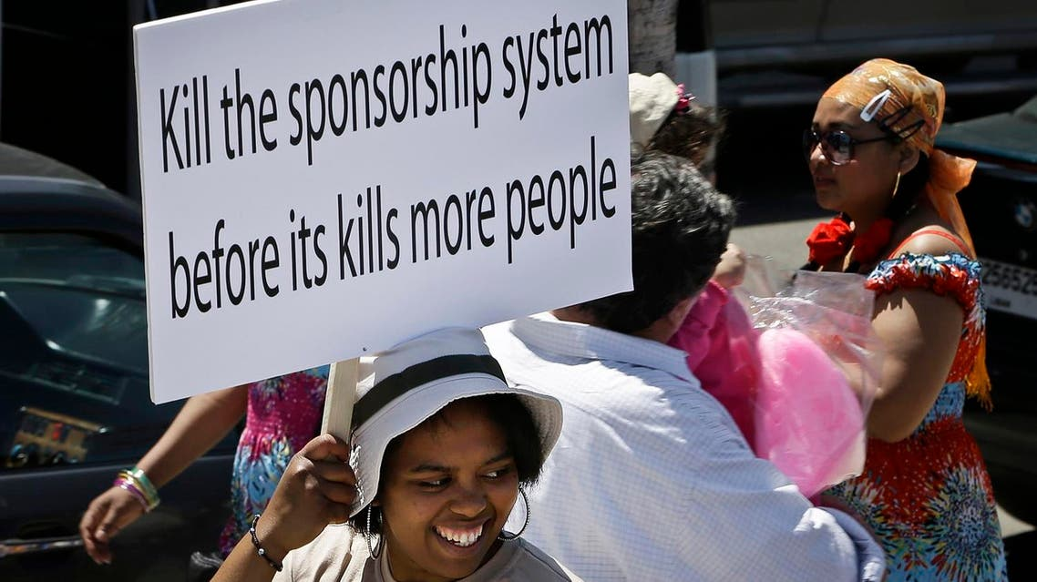 A migrant domestic worker, holds a banner demanding basic labor rights as Lebanese workers, during a march at Beirut's seaside, Lebanon, Sunday, April 28, 2013. (AP)