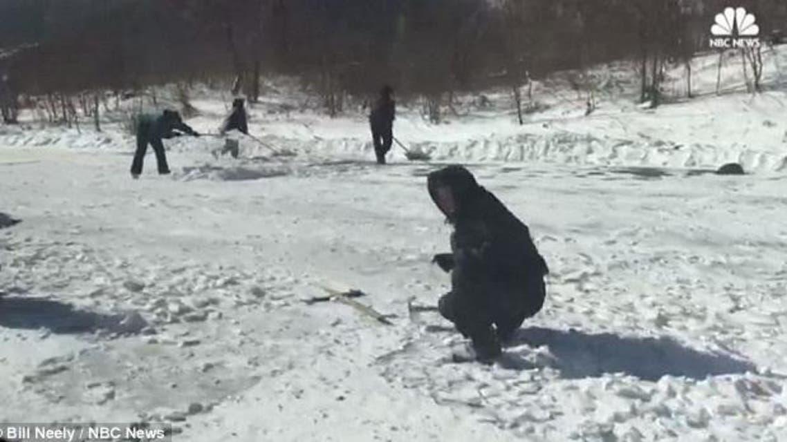 عمال كوريا الشمالية يزيلون الثلوج