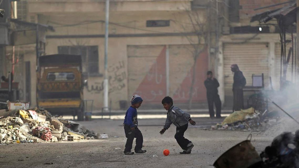 Boys play soccer next to a burning pile of garbage along a street filled with debris in Deir al-Zor, eastern Syria February 19, 2014. Picture taken February 19, 2014. REUTERS/Khalil Ashawi (SYRIA - Tags: CIVIL UNREST CONFLICT SOCIETY TPX IMAGES OF THE DAY)