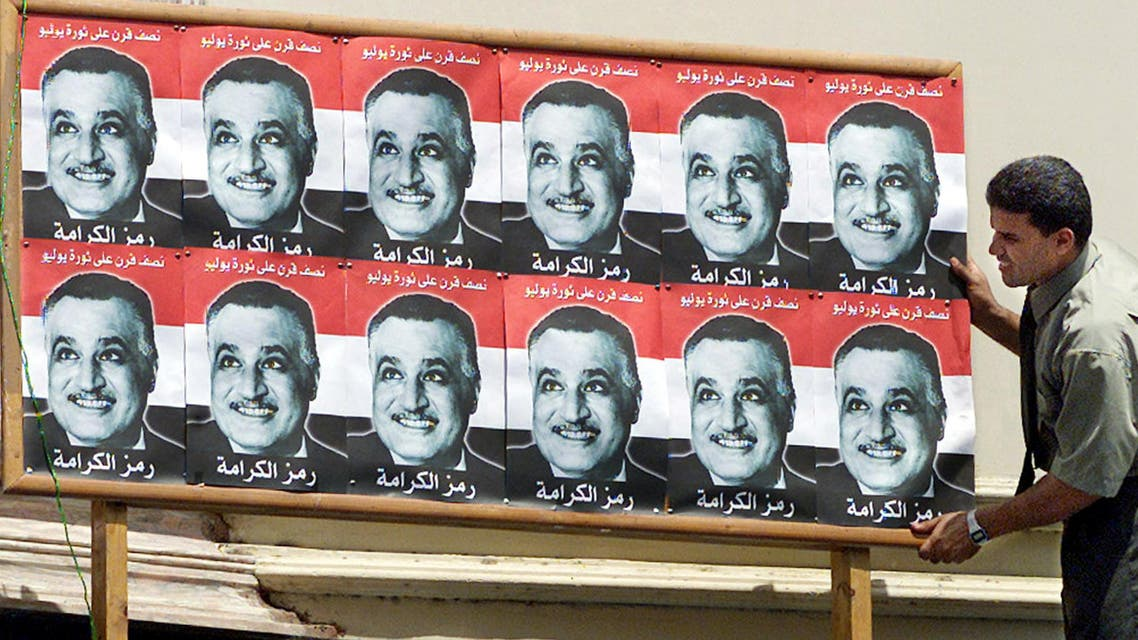 """An Egyptian man adjusts a billboard with pictures of former President Gamal Abdel Nasser's in Cairo July 23, 2002. Today marks the 50th anniversary of the revolution when the """"Free Officers"""", led by Nasser, seized power from the monarchy."""